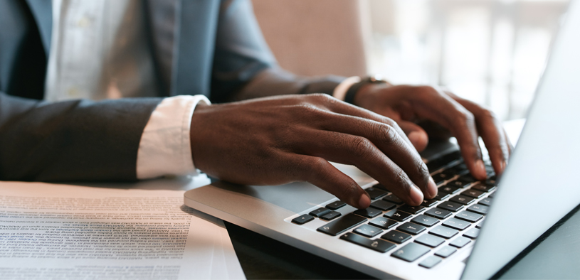 Businessman working on laptop with some documents on table. Close up on male hands typing on laptop keyboard.